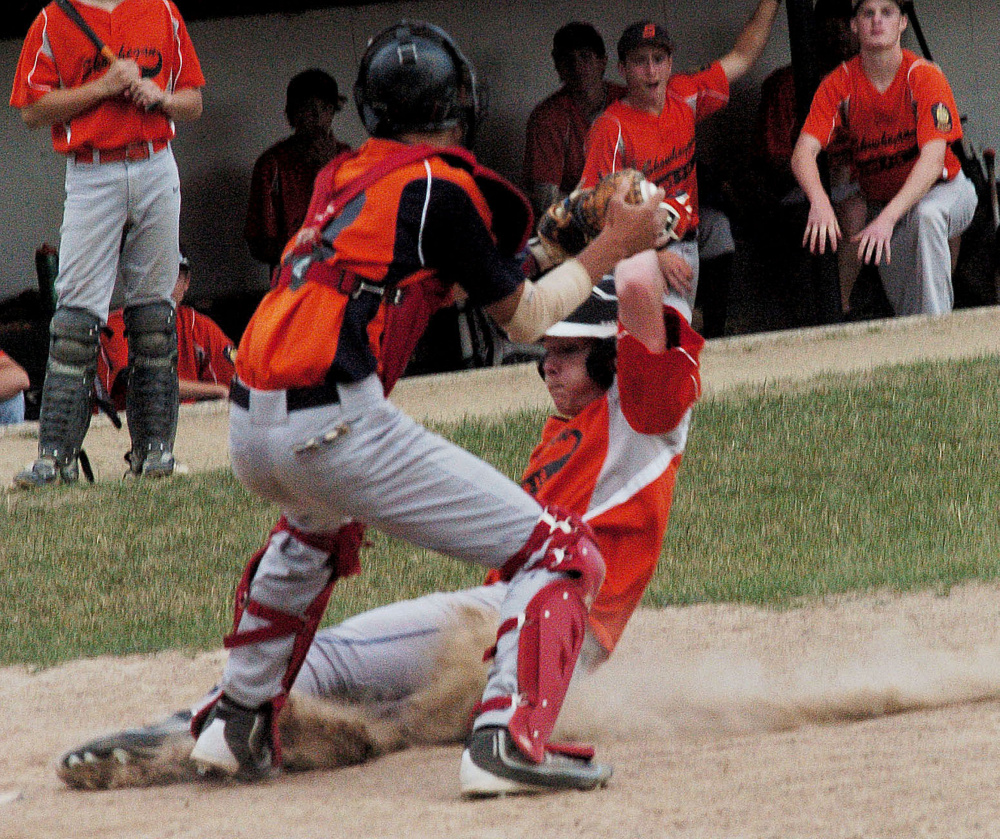 Skowhegan baserunner Tyler Noonan slides into home plate as Messalonskee catcher Percy Carey applies the tag during a junior American Legion game Tuesday at Memorial Field in Skowhegan.