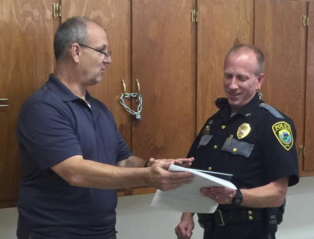 Clinton police Sgt. Stanley Bell, left, commends retiring Chief Craig Johnson last week at a retirement ceremony for Johnson. Bell will become the part-time chief Friday.