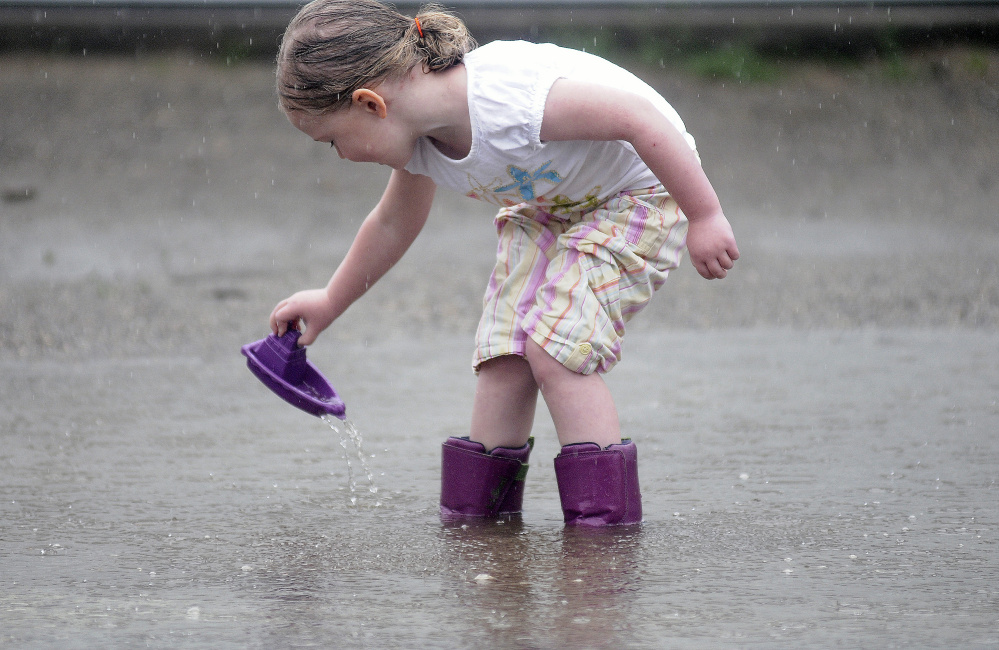 Emily Nichols, 4, launches a plastic boat Wednesday while tiptoeing through a puddle outside her Gardiner home.
