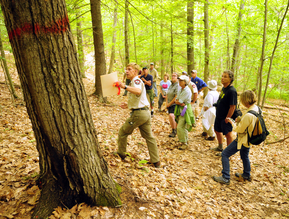 Department of Inland Fisheries and Wildlife Forester Eric Hoar, left with folder, leads a tour Tuesday of areas that will be cut at Jamies Pond Wildlife Management Area in Hallowell.