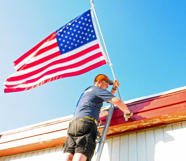 Nicholas Kimball straightens out the American flag last week at the fire house in Randolph. It's the same style as the ones that probably will go up in town Saturday now that a private donor has paid for additional liability insurance.