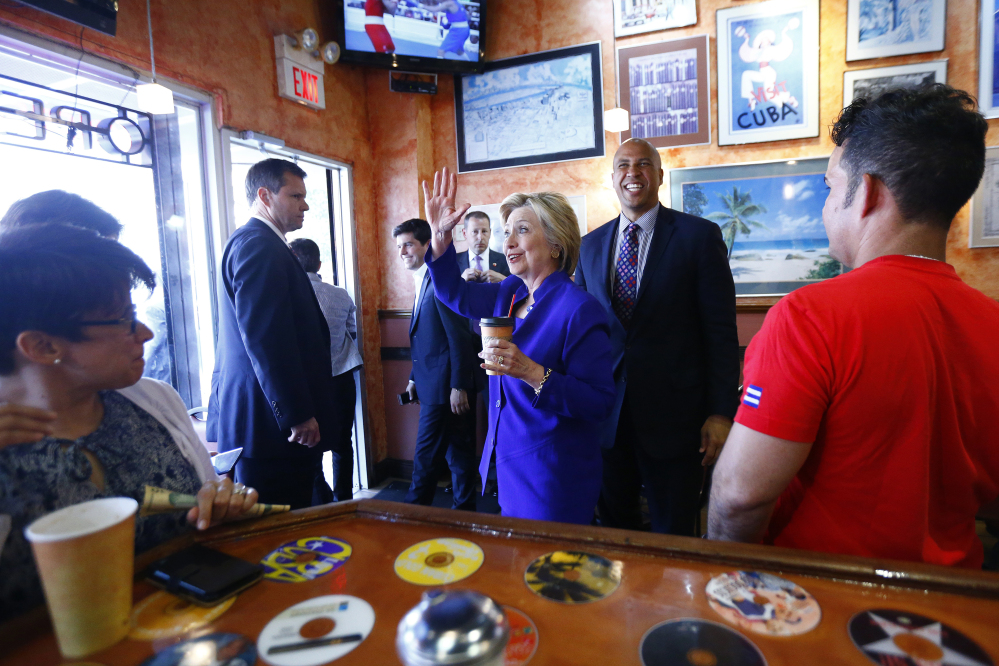 Democratic presidential candidate Hillary Clinton and Sen. Cory Booker, D-N.J., center right, make a stop at Omar's Cafe while campaigning Wednesday in Newark, N.J.