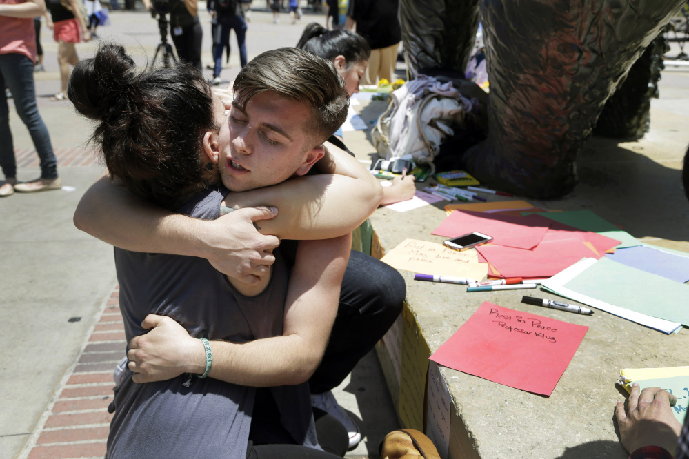 UCLA students Joseph Perez and Stephany Drotman hug after leaving condolence notes at the foot of UCLA's Bruin Bear statue on Thursday. Students wrapped up classwork and prepared for finals as the UCLA campus tried to regain a sense of normalcy a day after being rocked by a murder-suicide that prompted a lockdown and an enormous police response.