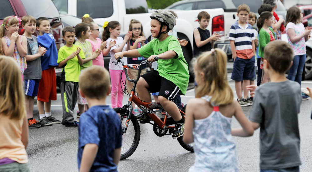 Nathan Lewis rides between lines of cheering students as he and his schoolmates  embark on the annual third-grade beach bike ride.