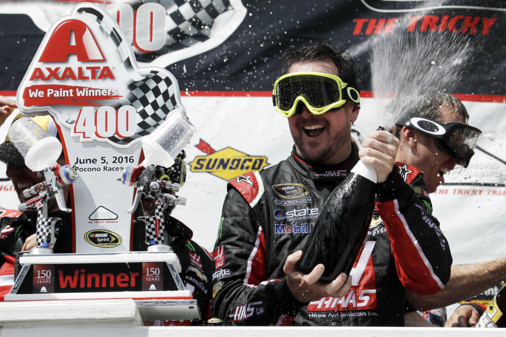 Kurt Busch celebrates with his team in victory lane after winning the NASCAR Sprint Cup race Monday at Pocono Raceway in Long Pond, Pennsylvania.