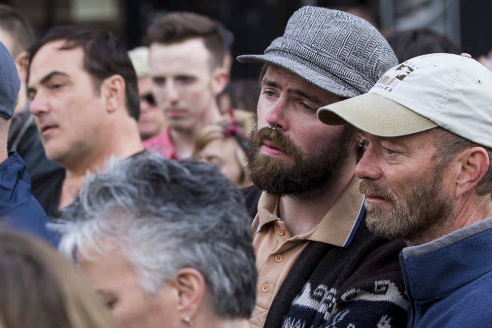 Couple Kevin Knieriem and Tim Mason, far right, embrace during Sunday's vigil in Monument Square to remember victims of the mass shooting in Orlando.