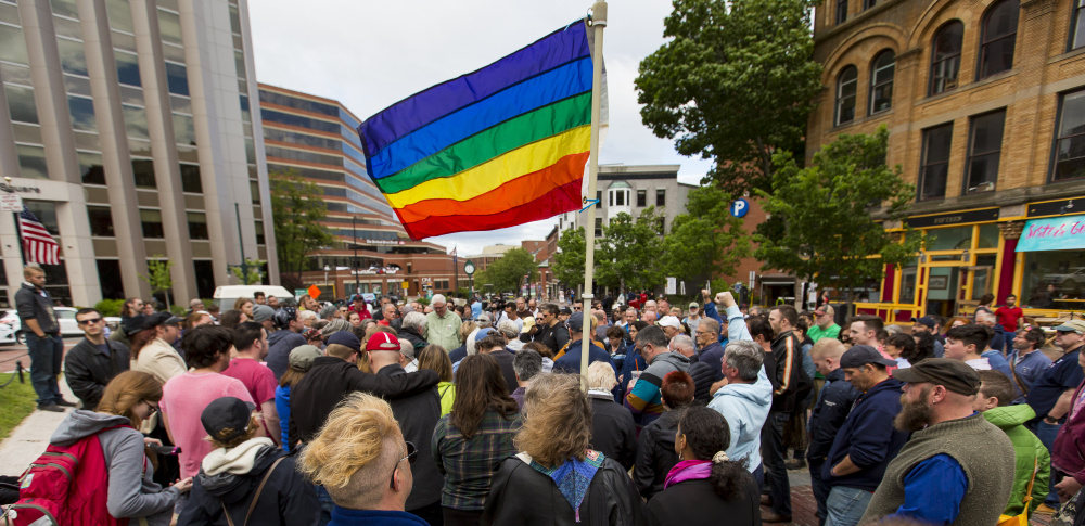 A pride flag flies over Sunday's vigil in Monument Square to remember victims of the mass shooting in Orlando.