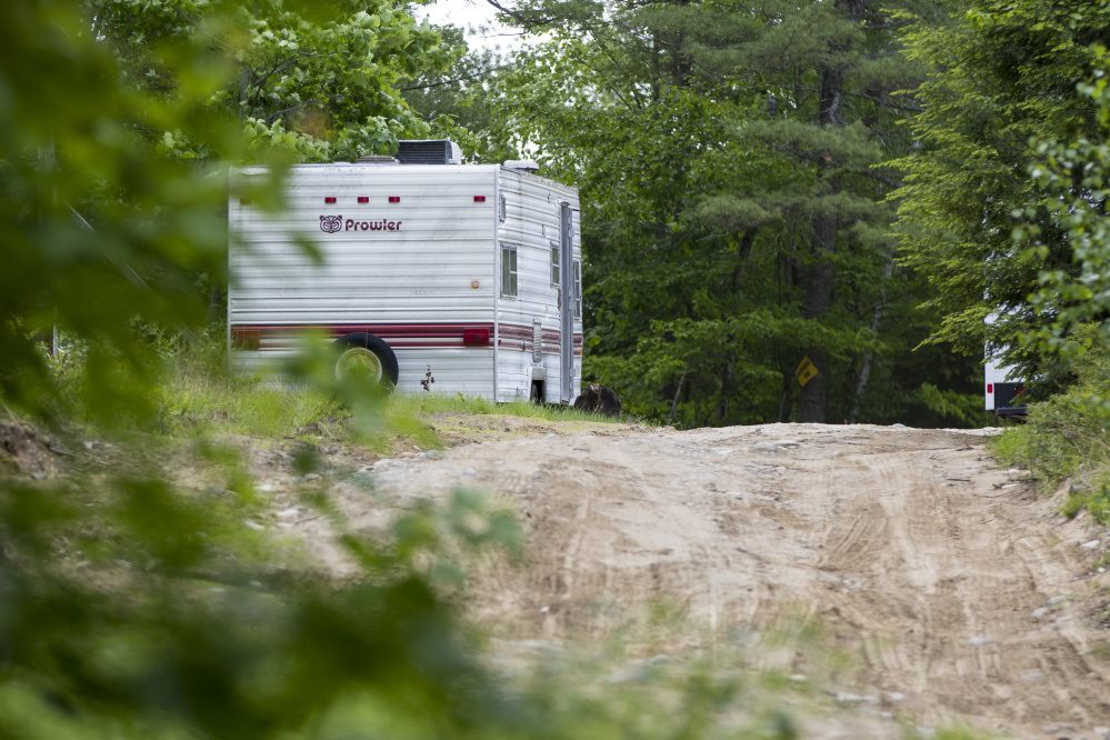 A camper sits parked at 540 Ossipee Trail in Limington, where Maine State Police investigated a homicide Sunday. The Evidence Recovery Team van is behind the trees to the right.