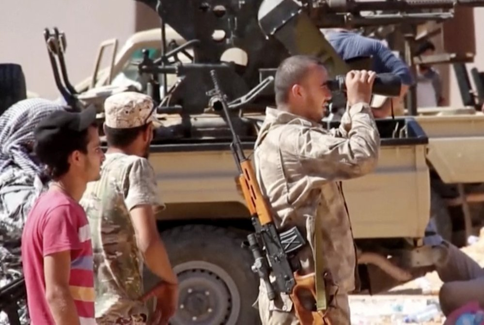 A pro-government fighter assesses the scene in the main street in Sirte, Libya, on June 14. But renewed clashes there have left 36 people dead, a hospital spokesman said.