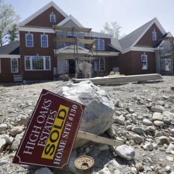 "A ""Sold"" sign rests in front of a house under construction, in Walpole, Mass. The Commerce Department reports on sales of new homes dropped in May."