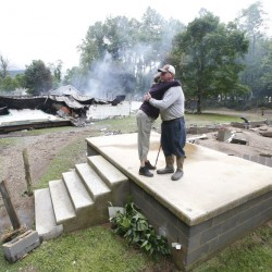 Jimmy Scott gets a hug from Anna May Watson as they clean up from severe flooding in White Sulphur Springs, W.Va., on Friday.