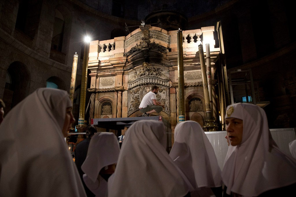 Christian nuns watch as a team of experts begin renovation of Jesus' tomb in the Church of the Holy Sepulchre in Jerusalem's old city on Monday. A team of experts has begun a historic renovation at the spot where Christians believe Jesus was buried, overcoming longstanding religious rivalries to carry out the first repairs at the site in over 200 years.