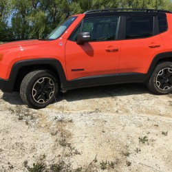 The 2016 Jeep Renegade Trailhawk in Omaha Orange has off-road capability but is more refined than the Wrangler.