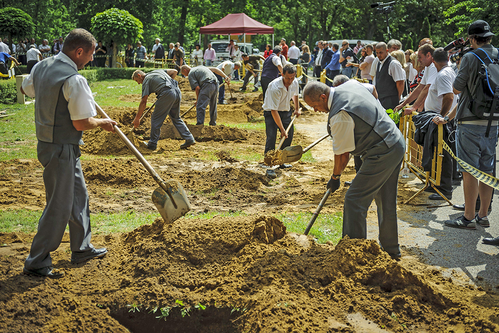 The first National Grave Digging competition takes place at the public cemetery of Debrecen, Hungary, Friday. Eighteen two-man teams are vying for a place in a regional championship to be held in Slovakia. Zsolt Czegledi/MTI via AP