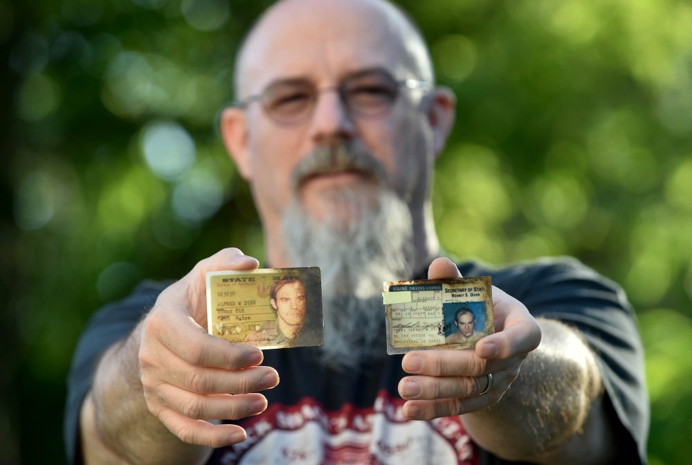 Al Dyer shows his 1980s driver's license and Bath Iron Works identification card Thursday at his home in Fairfield.
