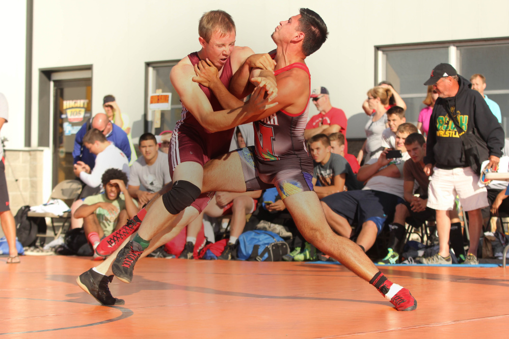 Nokomis Regional High School's Chris Wilson, left, battles Nebraska's Jacob Johnson during the 35th annual Maine-Nebraska wrestling exchange held Saturday in the Hight Chevrolet parking lot in downtown Skowhegan.