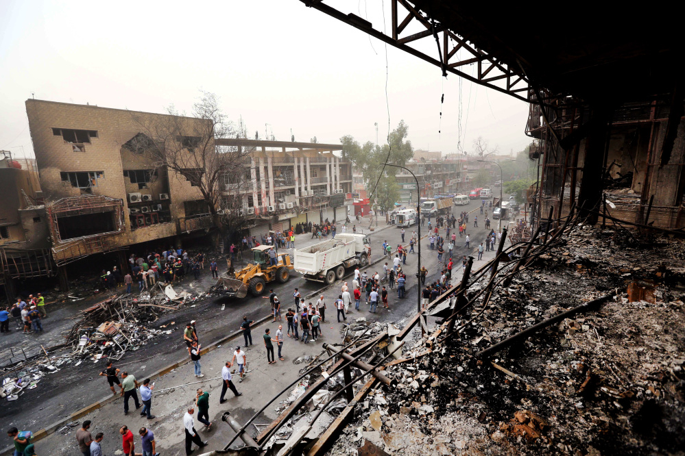 Iraqi security forces and civilians gather at the site after a car bomb hit Karada, a busy shopping district in the center of Baghdad on Sunday.