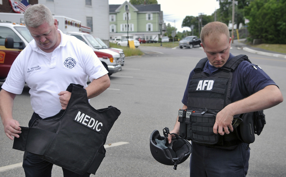 Augusta Fire Department Deputy Chief David Groder, left, with a safety vest and firefighter Anthony Thibodeau with a ballistic vest last week at Hartford Station in Augusta. The agency has been utilizing the vests for two years.