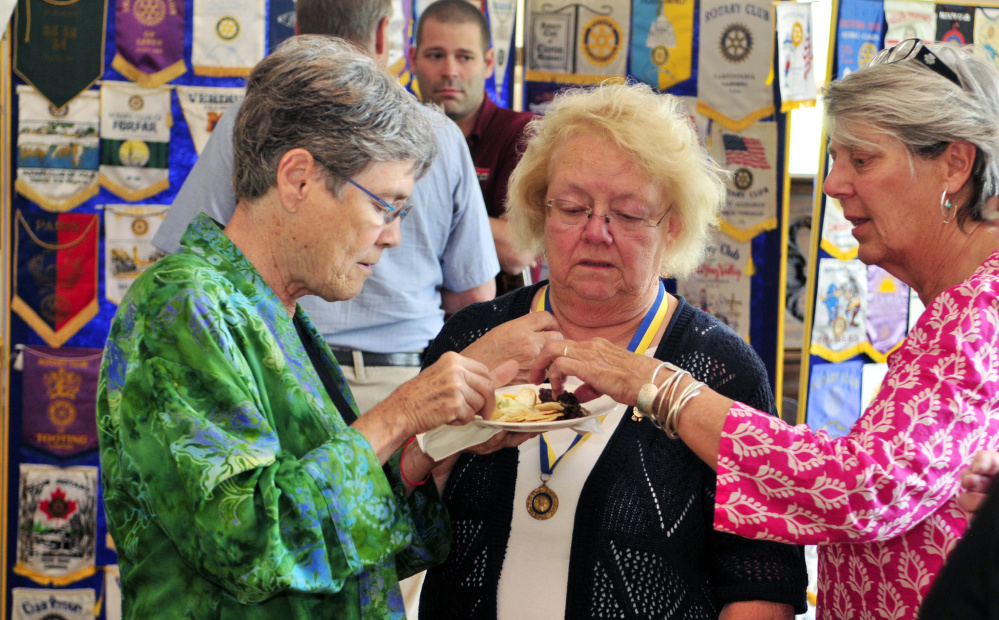 City councilor Dale McCormick, left, chats with Arlene Gagnon and Cheryl Clukey on Friday during the Augusta Rotary Centenary celebration at the Cohen Center in Hallowell.