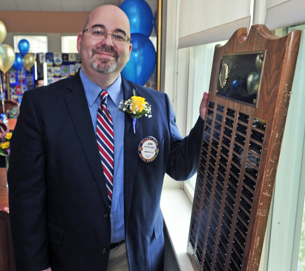 President John McLaughlin stands with a plaque listing the previous holders of his office over the last century on Friday during the Augusta Rotary Centenary celebration at the Cohen Center in Hallowell.