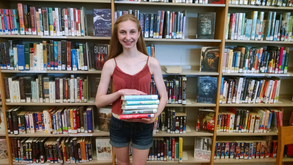 Miranda Sullivan holds a stack of books she has borrowed for the summer. The Messalonskee High School Library in Oakland is open for the summer between 10 a.m. and 2 p.m. Wednesdays. Students can borrow books and return them when school resumes in the fall. For more information, contact the high school at 465-7381.