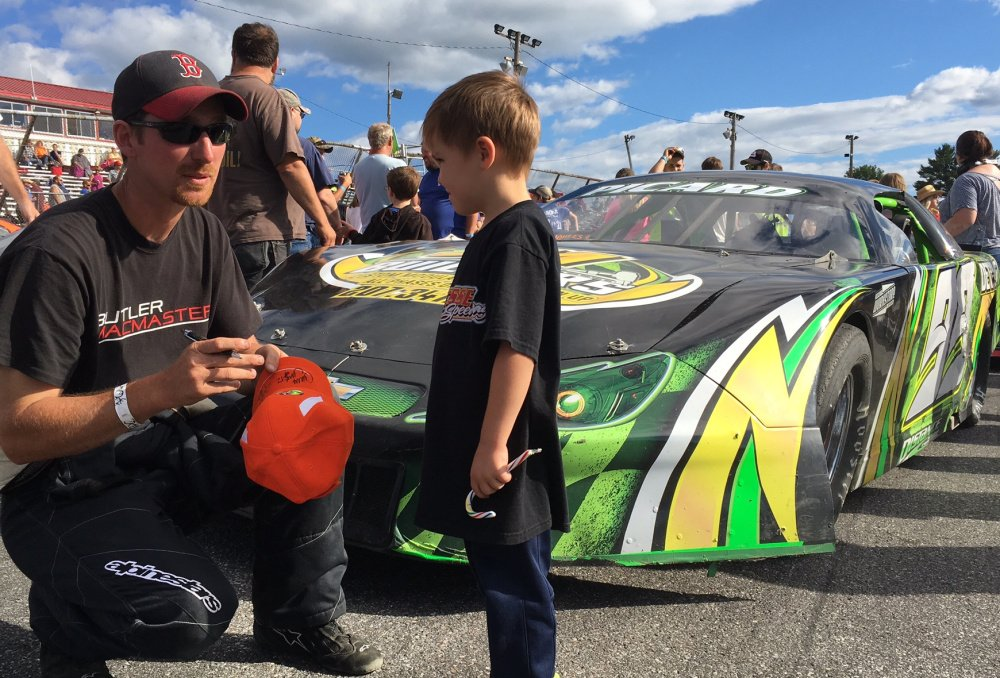Ajay Picard, of Palmyra, signs an autograph for a young fan at Wiscasset Speedway on Saturday. Picard sits second in the track's Pro Stock standings and is closing in on his first win.