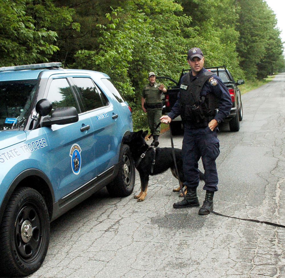 Maine State Trooper G.J. Neagle and his police dog, Draco, and Game Warden Steve Couture leave the woods on Bellsqueeze Road in Clinton after they found Michael Savage, who police said fled from a Hinckley Road home when police arrived in responding to an anonymous 911 call.