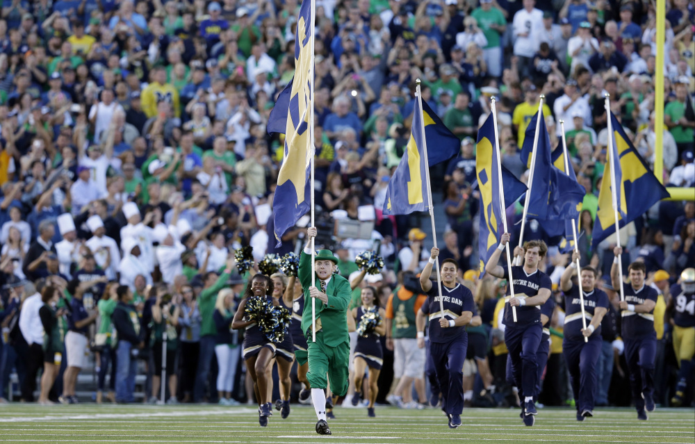 In this Sept. 6, 2014, file photo, the Notre Dame Leprechaun mascot takes the field before a game against Michigan in South Bend, Indiana. The two schools have reportedly agreed to resume their football rivalry.