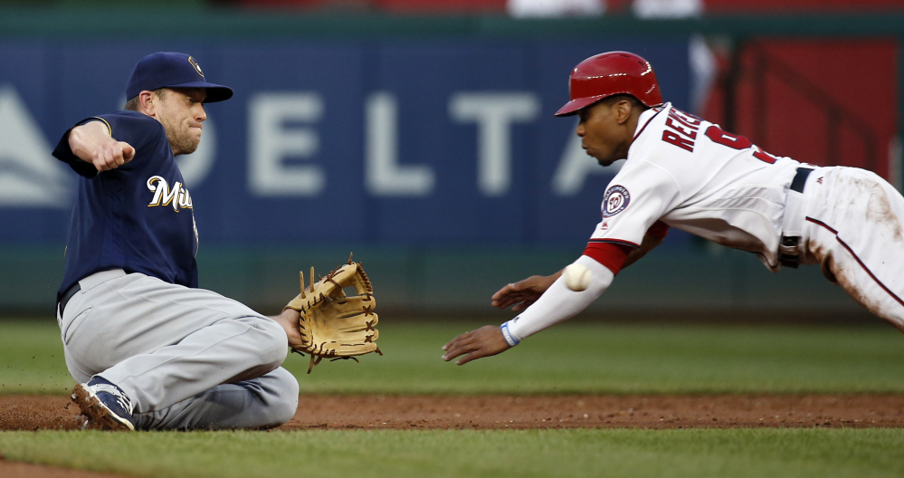 Milwaukee second baseman Aaron Hill waits for the throw from catcher Jonathan Lucroy and makes the tag for the out on Washington runner Ben Revere during the third inning Tuesday in Washington. The Red Sox acquired Hill on Thursday.
