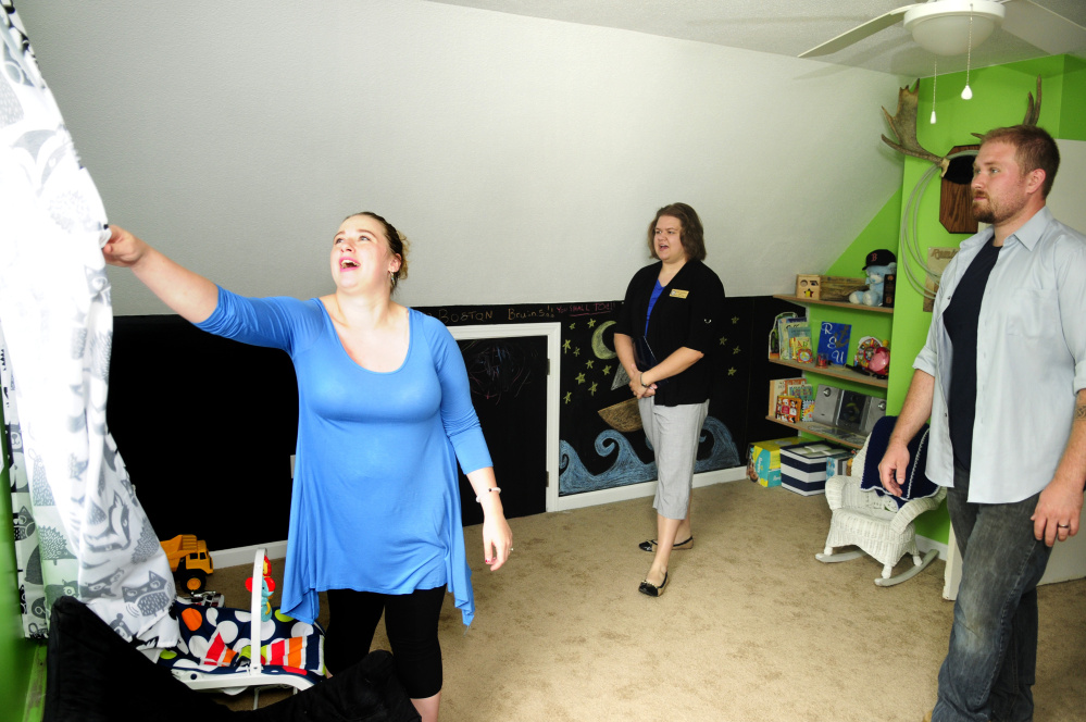 Abby Utecht, left, and Steve Utecht show Sarah Graettinger, a staffer from U.S. Sen. Angus King's office, the nursery of their new home after a news conference Friday in Richmond.