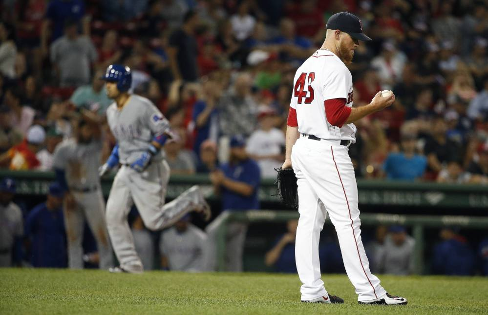 Boston Red Sox' closer Craig Kimbrel examines a new ball after giving up a three-run home run to Texas' Robinson Chirinos, left, during the ninth inning Tuesday at Fenway Park.