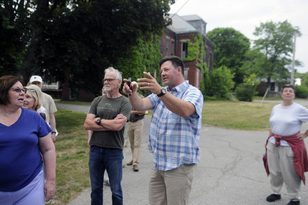 Matt Morrill, center, describes a public road he wants to build for a housing development at the Stevens School complex in Hallowell during a recent tour of the property.