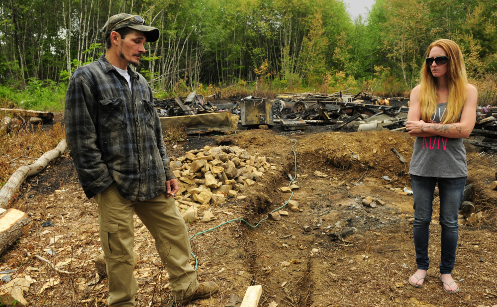 Fire victims Eric and Kristie Baker stand on their property in Gardiner last week after a fire destroyed their home. Police arrested Joseph Manganella, 35, of Gardiner on Friday on a charge of arson related to the case.