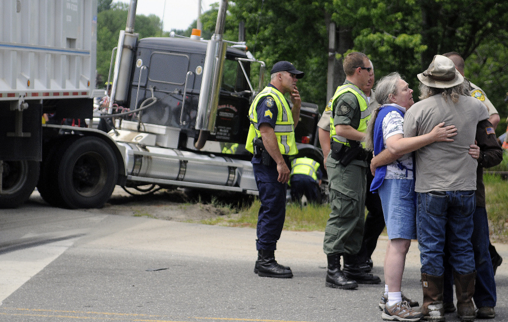 Friends and family of people injured in a collision Tuesday console each other on Route 126 in Litchfield. One person in a passenger car that collided with a tractor-trailer died at the scene while two others were taken to area hospitals.