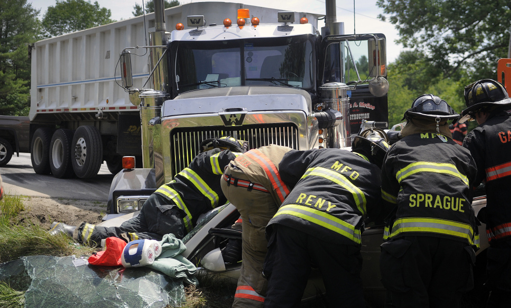 Firefighters extricate two people trapped Tuesday in a vehicle that collided with a tractor-trailer on Route 126 in Litchfield. One person in the vehicle died while two others were transported to area hospitals. The driver of the truck was uninjured.