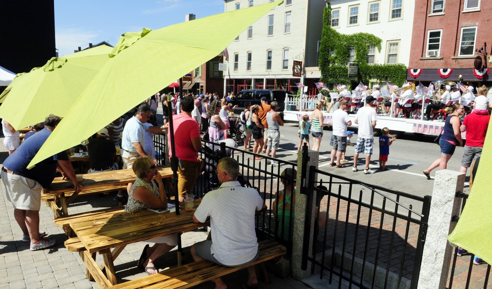 People on the Quarry Tap Room deck watch the Hallowell Community Band go by Saturday at the start of the 2016 Old Hallowell Day parade. The deck was under construction for a few weeks and was completed just in time for Old Hallowell Day.