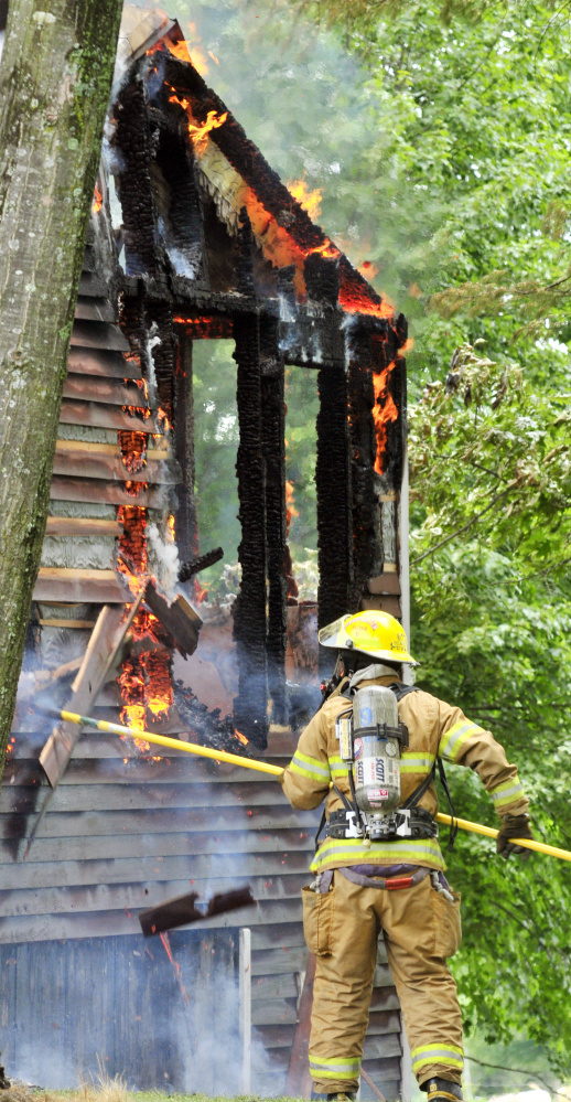 A firefighter pulls off siding to expose flames Sunday at 35 Holway Road in Sidney.