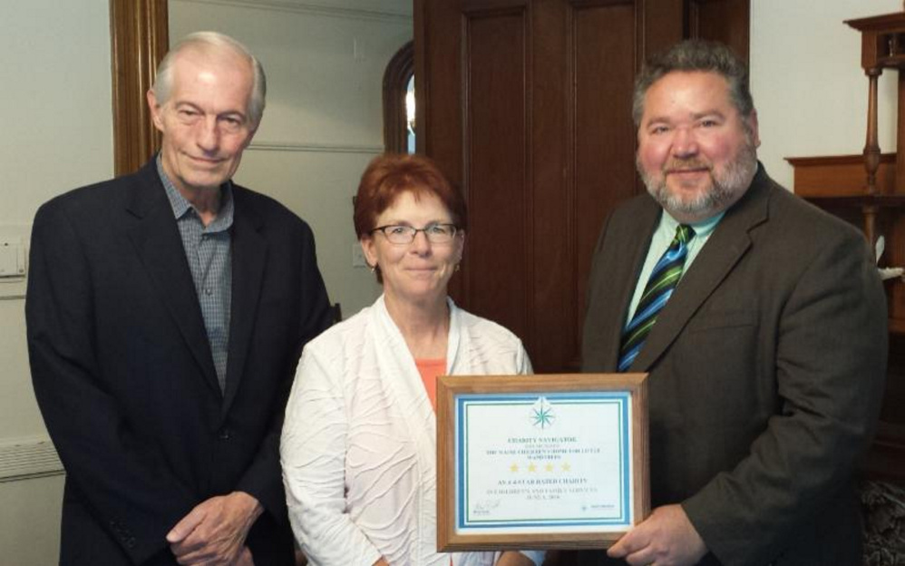 The Maine Children's Home for Little Wanderers' Stephen Mayberry, development director, left; Diana Rafuse, finance director, center; and Rick Dorian, executive director, right, with The Maine Children's Home's Charity Navigator 4-star certificate.