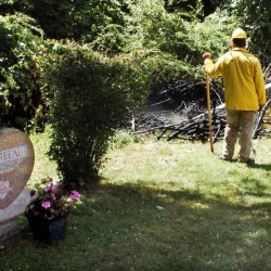 Waterville firefighters extinguish a fire in brush beside gravesites at the St. Francis Cemetery in Waterville on Thursday. Police said Friday they have a suspect in both that fire and an earlier one at adjacent Pine Grove Cemetery.