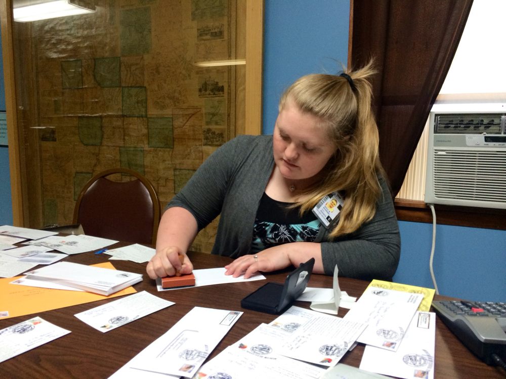 Postal worker Kayla McKenney stamps a letter at the Moscow Town Hall Friday morning. McKenney, who normally supervises the nearby Caratunk post office, was working in Moscow for the day as part of a special event in the town with no post office.