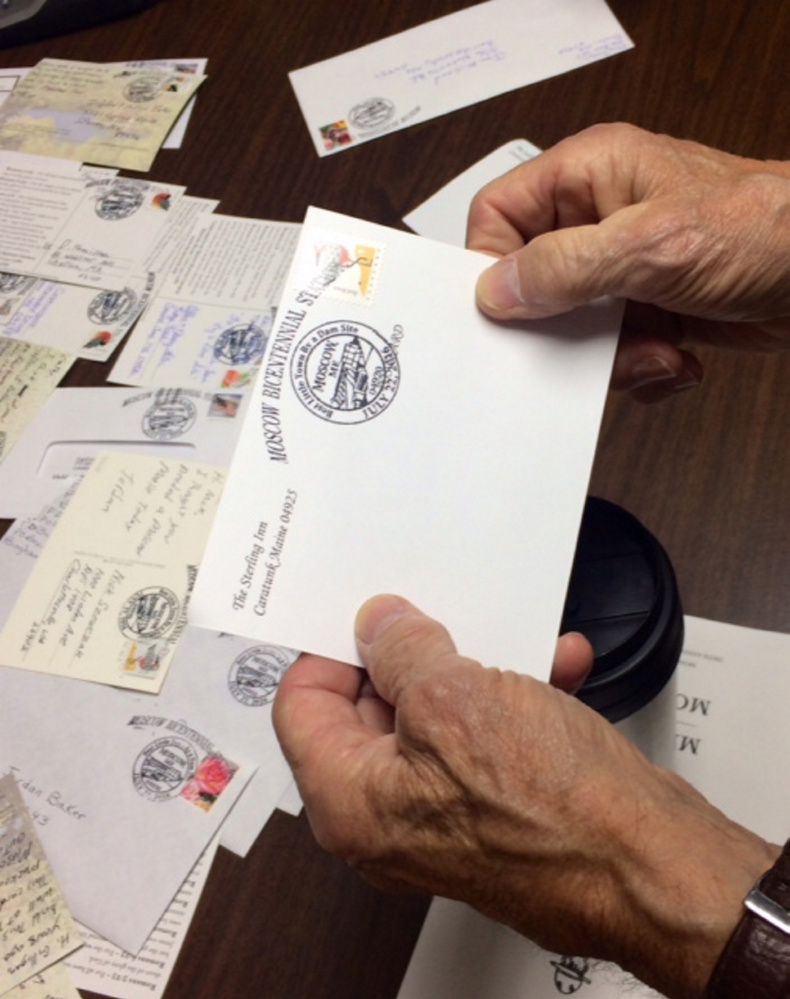 A visitor to Moscow holds an envelope stamped with the special pictorial postmark designed for the town's 200th anniversary celebration at the town's temporary post office Friday.