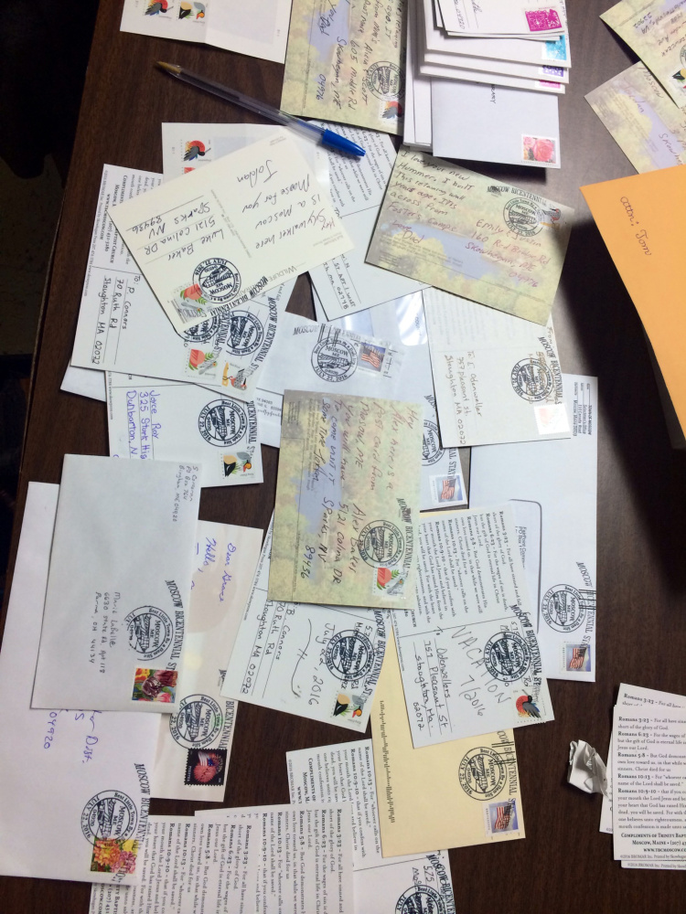 Postcards and envelopes clutter a table at the Moscow Town Hall that served as a temporary post office Friday.