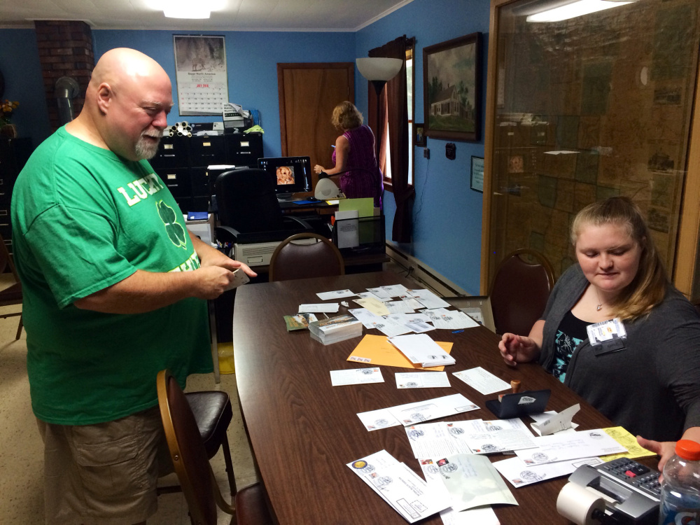 Bingham resident Jordan Baker, left, pays for his mail at Moscow's temporary post office Friday morning. The town doesn't have a post office, but a temporary one was set up this weekend as part of its bicentennial celebration, and residents took advantage.