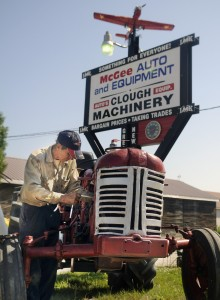 CAP.cutline_standalone:Delbert Clough changes belts Thursday on a tractor that's for sale at his firm in West Gardiner. Clough fixes and sells several tractors a year, including this International model with a mower from the 1950s.