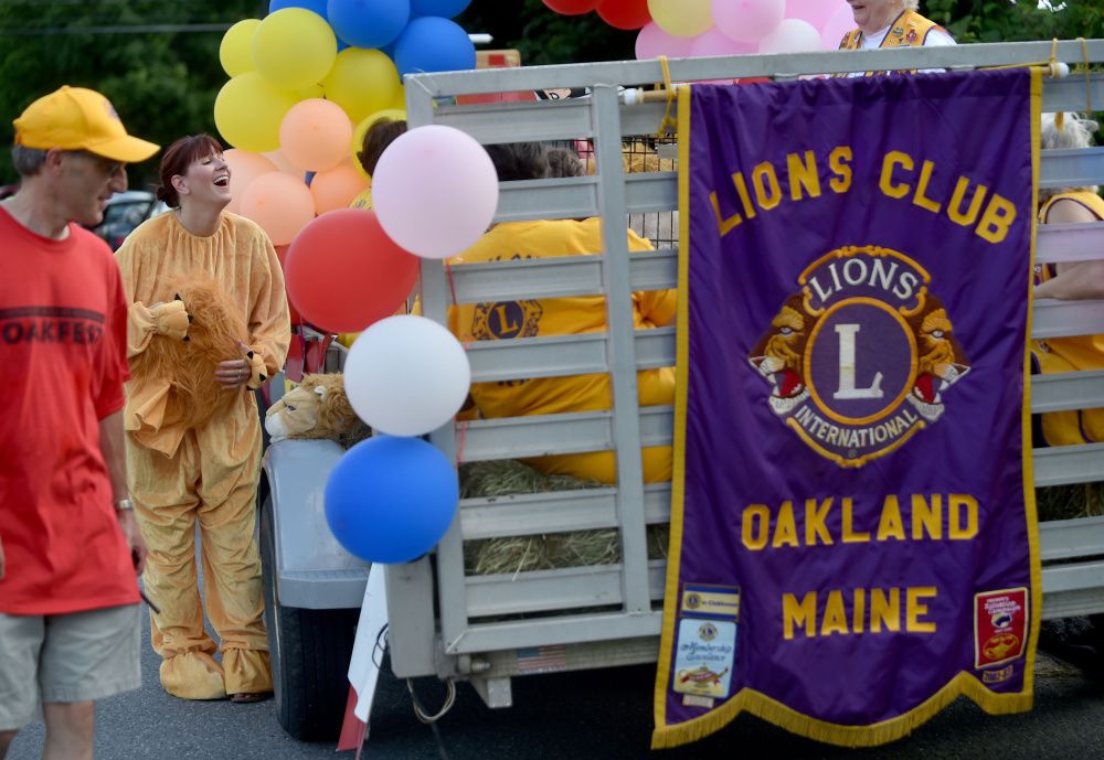 Lynne Hamilton, left, smiles as she puts on her Oakland Lion's Club costume next to the Lion's Club float as she prepares for the Oakfest parade in Oakland on Friday.