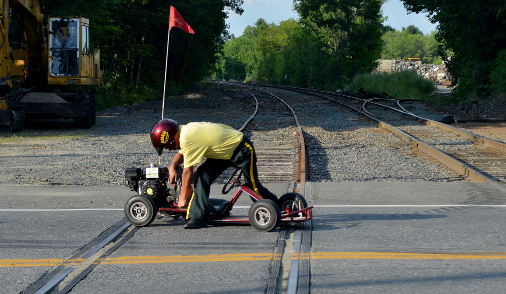 A Kora Shriner tries to start his stalled go-cart on the railroad tracks during the OakFest parade in Oakland on Friday.