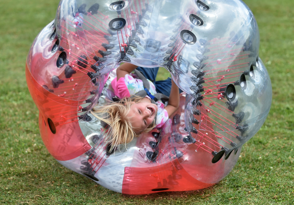 Kaydence McKenney, 6, gets knocked over in her knockerball during OakFest at Williams Elementary School in Oakland on Saturday.