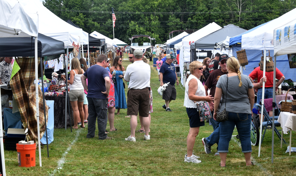 People browse the vendors' tents behind Williams Elementary School during OakFest in Oakland on Saturday.