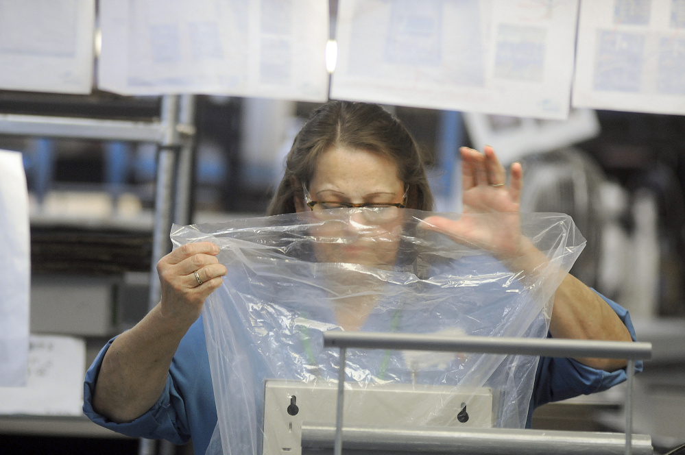 Tricia York packages a product after testing it at Alternative Manufacturing Inc. in Winthrop Wednesday.