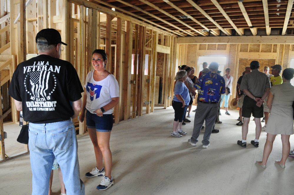 Kelsey Mills, wife of Travis Mills, second from left, chats with visitors during a tour on Saturday at the Travis Mills Foundation's Maine Chance Lodge in Mount Vernon and Rome.